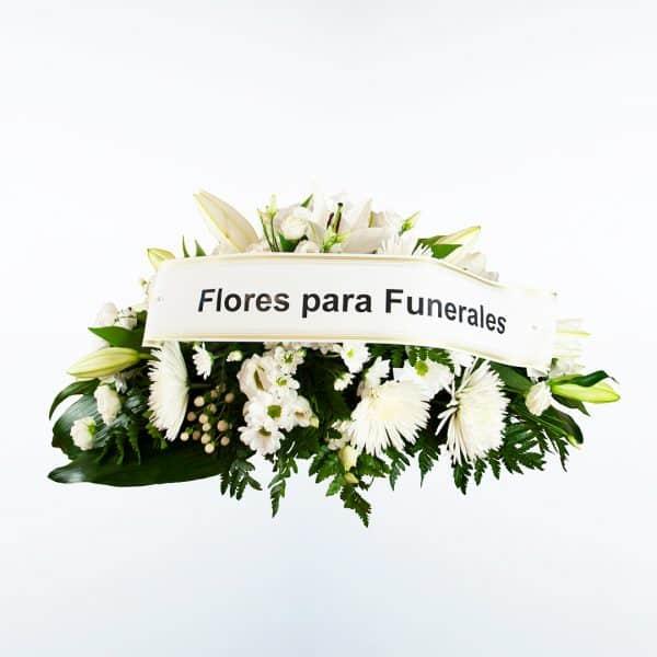 Centro de flores blanco para funeral en tonos rojos y blancos a domicilio en Madrid y Toledo con cinta de condolencias.