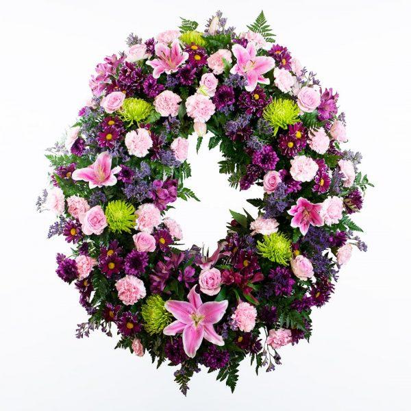 Corona de flores morada, verde y rosa para enviar a tanatorios de madrid y toledo.